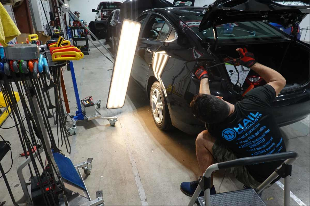 pdr-tech-working-on-hail-damaged-car-in-mckinney